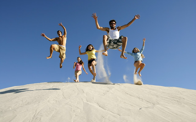 Happiness With Friends Jumping On Sand