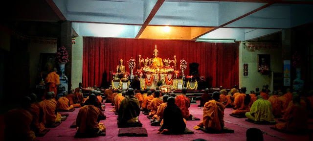 Buddhist monks reciting prayers in front of gold colored metal statue of Gouthama Buddha, Mahabodhi Society, Bangalore