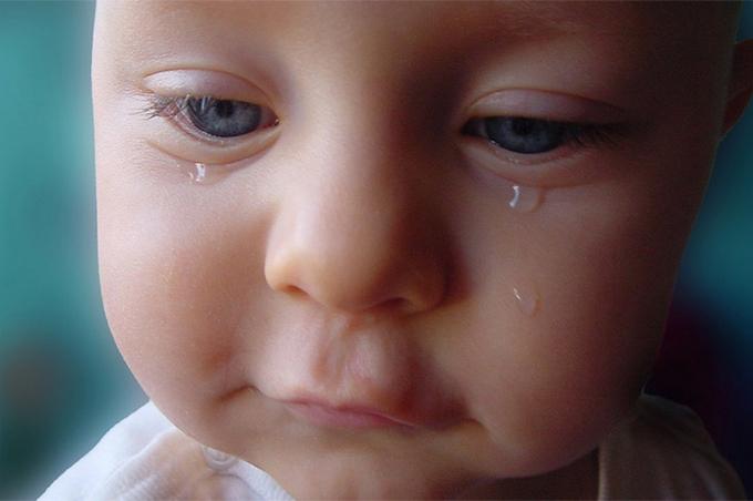 صورة طفل بعيون زرقاء يبكي بصمت