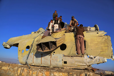 Afghan children play over the wreckage of an old Soviet-era tank in Ghazni on November 15, 2013. Tens of thousands of children in Afghanistan, driven by poverty, work on the streets of the war-torn country's cities and often fall prey to Taliban bombings and other violence, as well as abuse