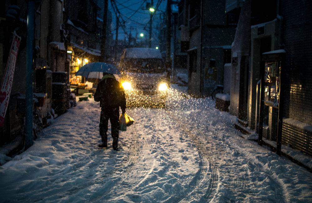 夜、吹雪の中帰宅している写真