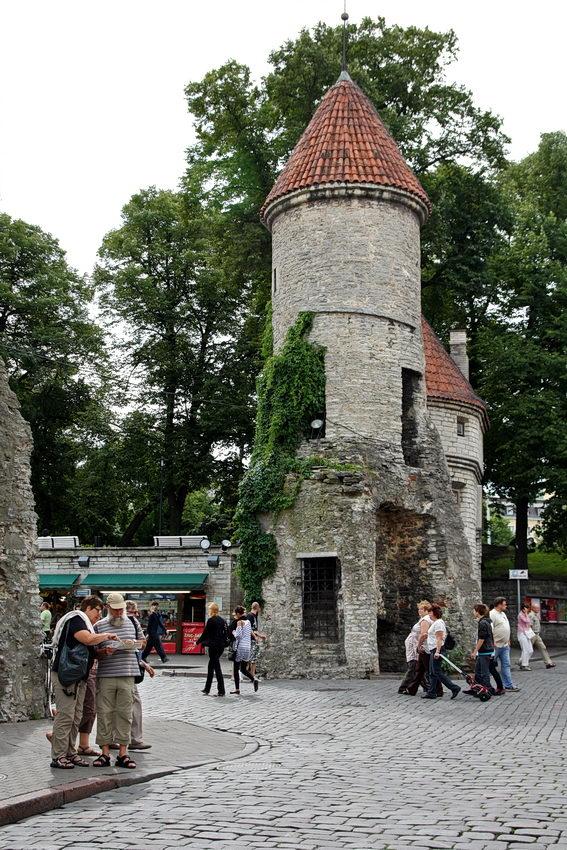 Foto das torres redondas que fazem parte da entrada da cidade velha de Tallinn. Várias pessoas em circulação