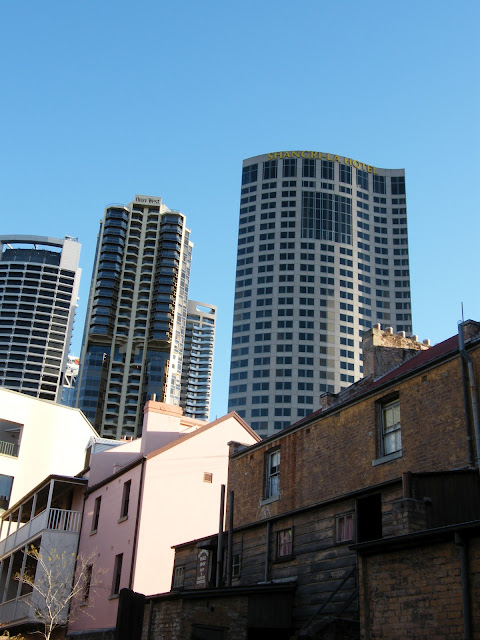 Juxtaposition of historic Rocks houses next to skyscrapers of downtown Sydney