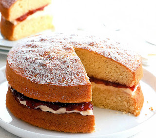 Traditional victoria sponge sandwich with a cream and strawberry jam filling with one slice removed