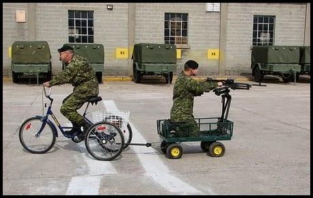 Dos militares en una bicicleta con una metralladora.