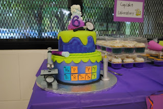science birthday cake with a microscope and element letters