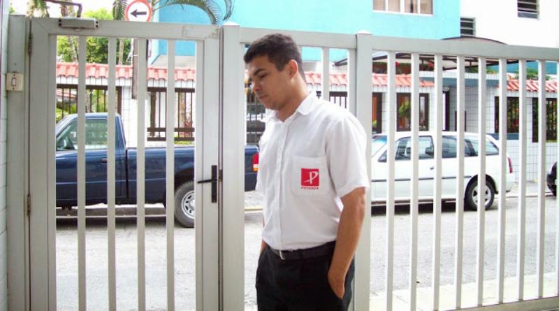 Jota Fagner vestindo seu uniforme de porteiro, com camisa branca e calça preta. As mãos no bolso e um logotipo vermelho com uma letra P em branco no bolso da camisa. Foto tirada na portaria em que ele trabalhava em 2008. Ao fundo se vê a grade do prédio e por trás dela um carro preto com carreceria, semelhante a uma D20.