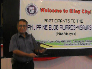 Gil Camporazo holds a plow as a token from the Negros Bloggers in recognizing him as one of the best bloggers in the Visayas in 2011