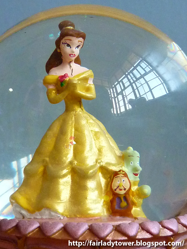 This Beauty and the Beast snowglobe features a handpainted Belle standing on