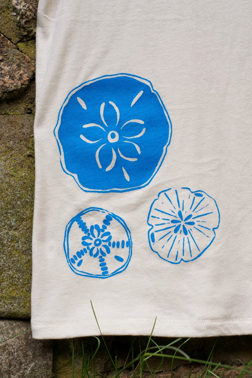 Sand dollar design in blue on the new natural organic cotton tee.