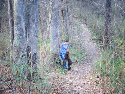 Looking down a winding woodsy path, you can see Beth smiling & leaning against a tree while Alfie dances on his hind legs