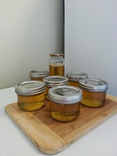 Seven finished jars of golden yellow jelly.
