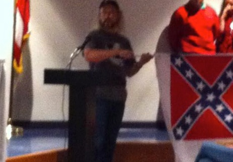 Sonny Thomas holding a Confederate flag at the school board meeting, from Nimisha Patel
