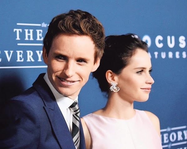 Felicity Jones with Eddie Redmayne in Alexander McQueen Pre AW14 blue one-button suit with McQueen shoulder and silk check tie to attend the premiere of 'The Theory of Everything' in Los Angeles, on Tuesday 28th October 2014