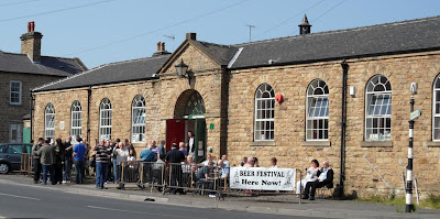 A long low stone built buiding with huge arched windows set either side of a central door, people are outside on the verge drinking and there is a banner advertising the beer festival hung on the pedestrian barriers