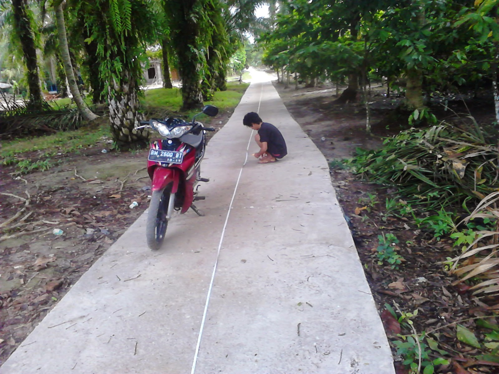 Vido Septa Hidayat mengukur jalan yang telah disemenisasi di Desa Seresam
