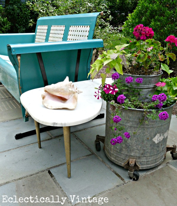This vintage tin planter, bright blue bench, and marble side table give this porch decor a very eclectic theme