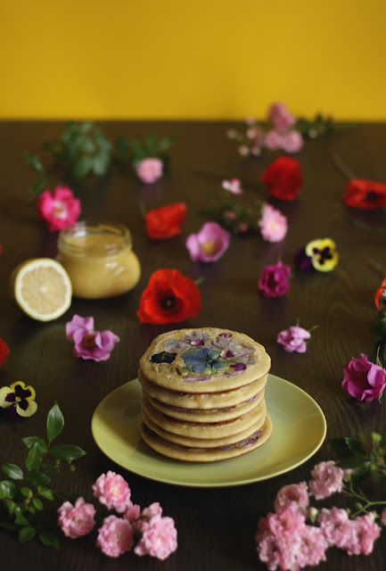 Deliate pancakes with edible flowers in the batter accompanied by homemade lemon curd - recipe brought to you by the german foodblog Pancake Stories!