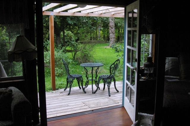 French doors leading to outside wood deck with table and chairs
