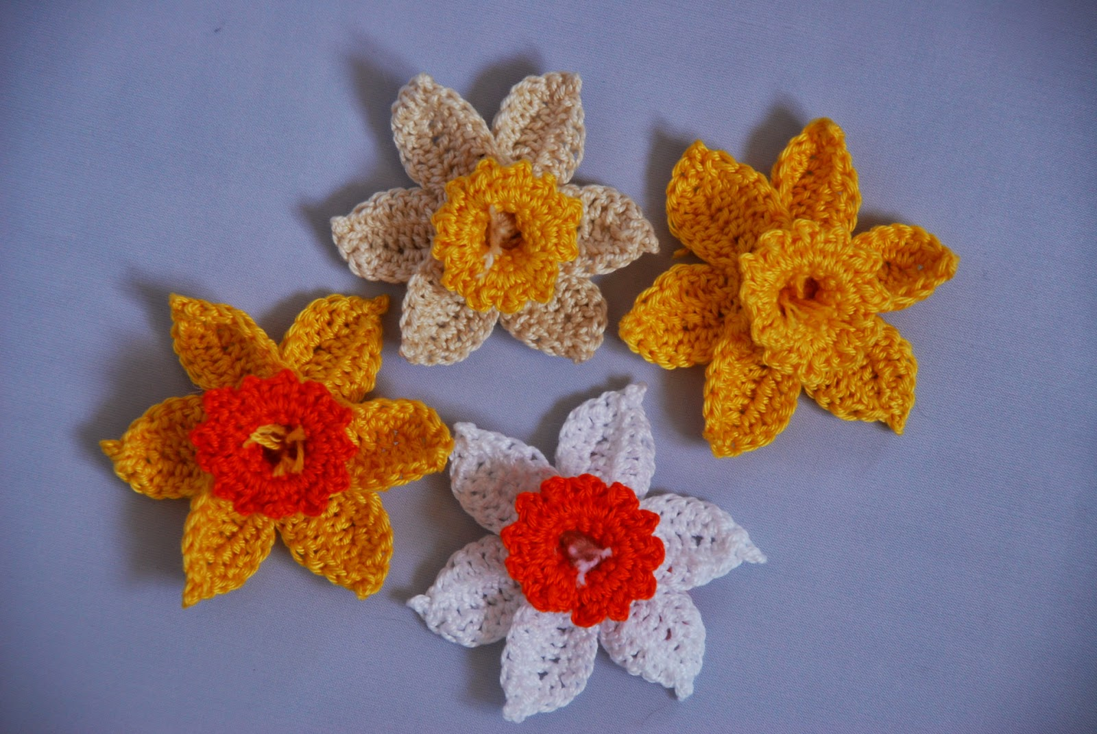 Crochet Daffodil pattern and tutorial: image of four different coloured daffodils