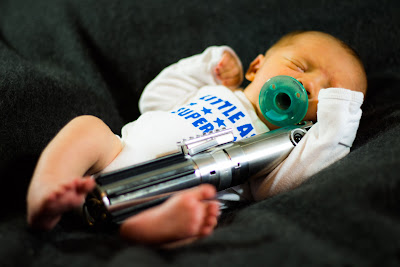Newborn baby with a Luke Skywalker lightsaber.