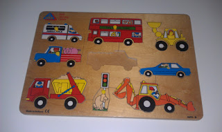 A baby slot-in jigsaw board puzzle with a missing piece.