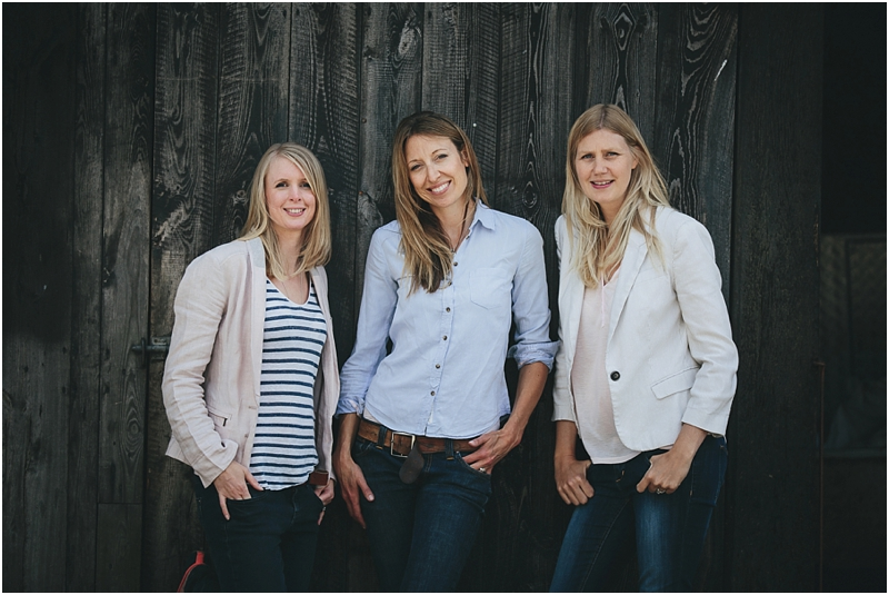 Three women standing by a wooden barn door