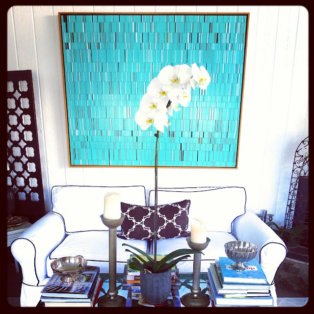 Art by Brian Wills in Coco of COCOCOZY's living room with a white sofa with brown piping