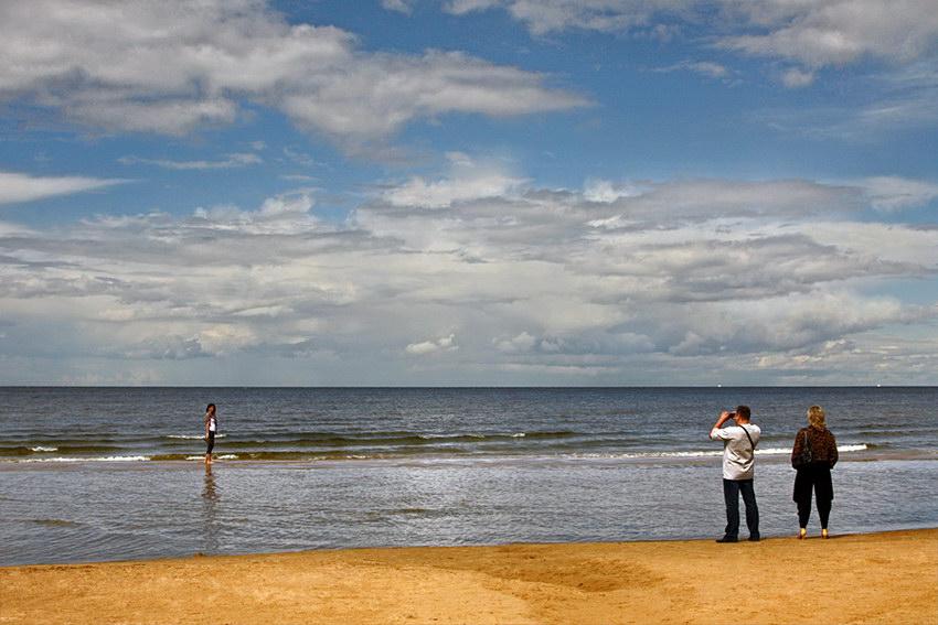 Foto da praia com águas de baixa profundidade. Um casal a tirar fotos a uma rapariga na água, de pá, com os sapatos na mão. Céu nublado mas luminoso