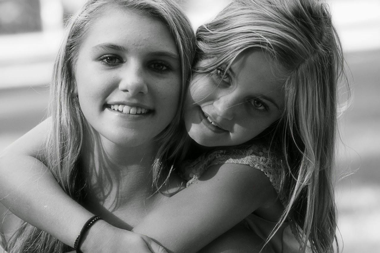 Portraitfoto: zwei junge Frauen lächeln in die Kamera, während eine die Andere von hinten umarmt.