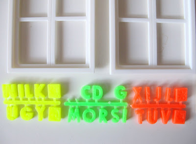 Three sets of coloured plastic letters, arranged under two dolls' house miniature windows.