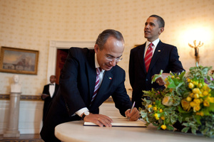 photo President Calderon signs as President Obama looks on