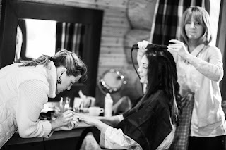 Bride having her nails painted and her hair curled on the morning of her wedding