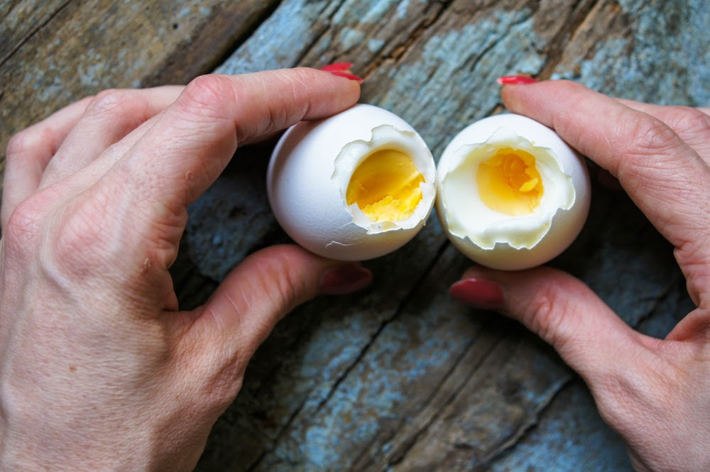 Soft boiled eggs broken open to reveal the yolk inside. Eggs are a versatile food that can compliment any meal.