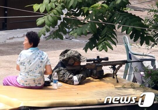 Francotirador coreano al lado de una ajumma