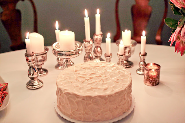 close up of birthday cake surrounded by candles in mercury candlesticks