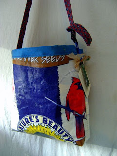 Large, colorful tote bag. The front has a dark blue stripe down the middle and a white stripe on either side. One of the white stripes is mostly filled with a bright red cardinal. The bottom of the bag has a semi-circle that says Nature's Beauty and shows part of a yellow sunflower below it. There is a narrow strip of brown at the top with white writing that says an indistinguishable word and then seeds. The fabric lining is blue and the shoulder strap appears to be a reddish-blueish paisley tie.