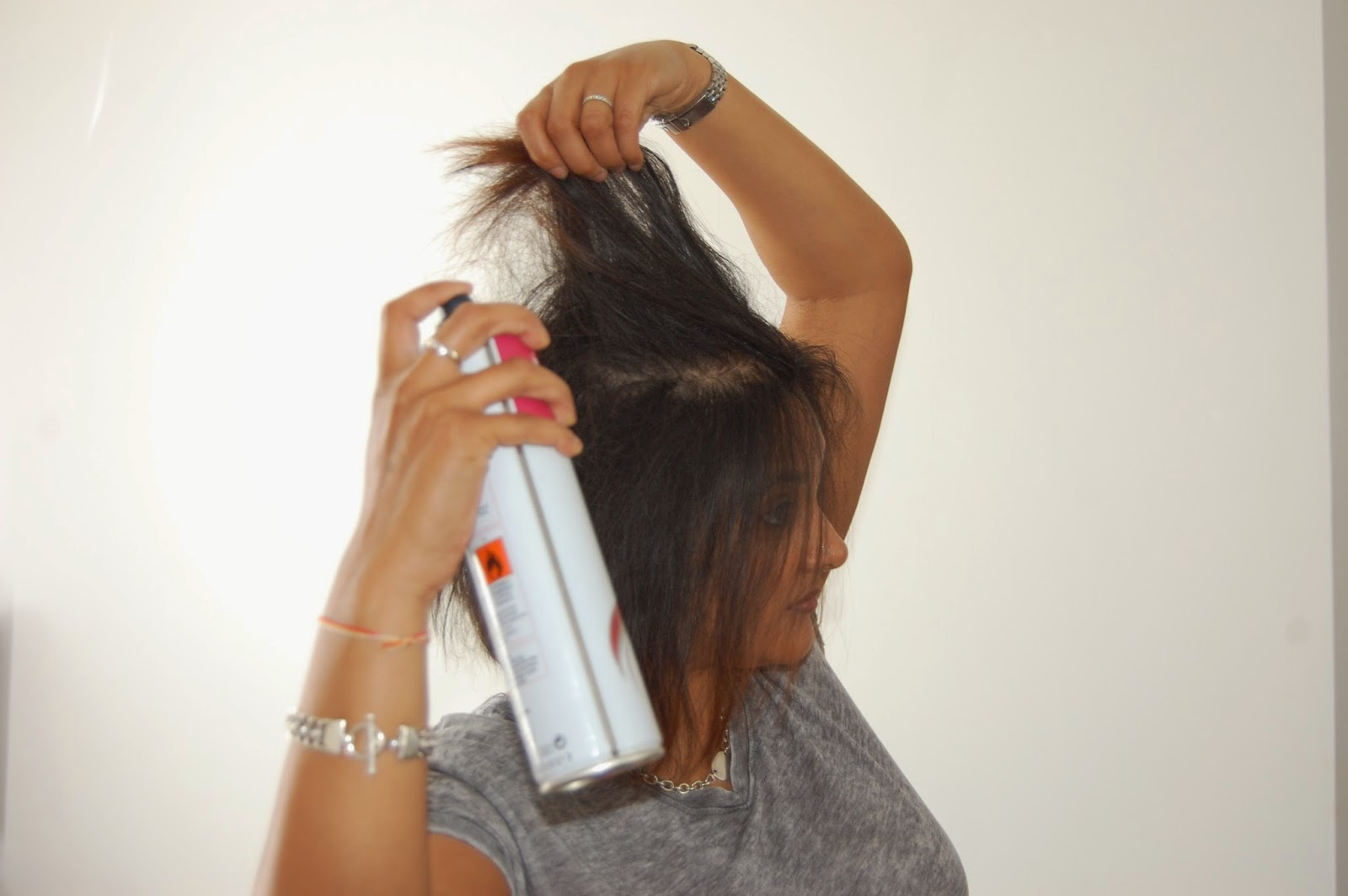 Spray hair to get extra volume