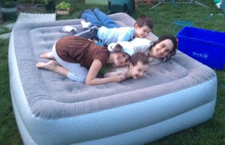 family on queen air matress in the back yard