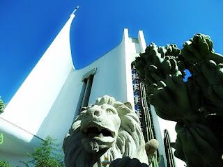 Igreja Matriz de São Marcos. Escultura de leão em pedra e cactus em frente à igreja construída em estilo moderno.
