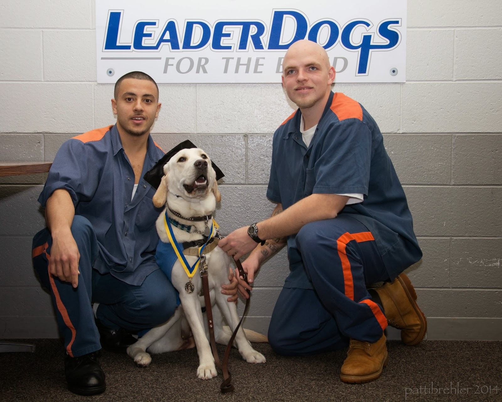 Two men are kneeling on one knee with a yellow lab sitting down between them. The men are wearing blue shirts and blue pants with orange sripes on the shoulders and legs. The dog is wearing a black graduation cap and has a yellow and blue ribbon around its neck wth a medal. A white poster is on the wall behind them that says Leader Dogs for the Blind.
