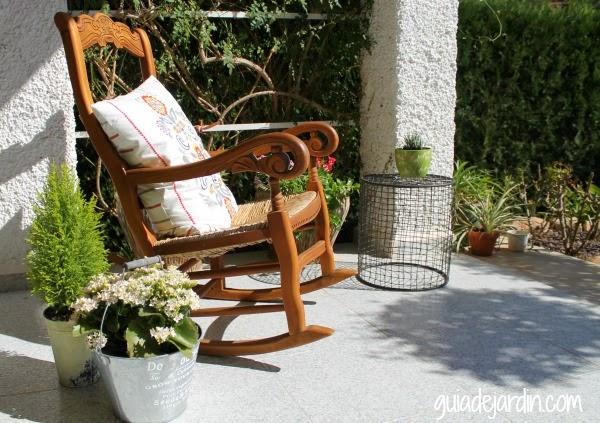 Mecedora en el porche junto a kalanchoe y pequeño ciprés