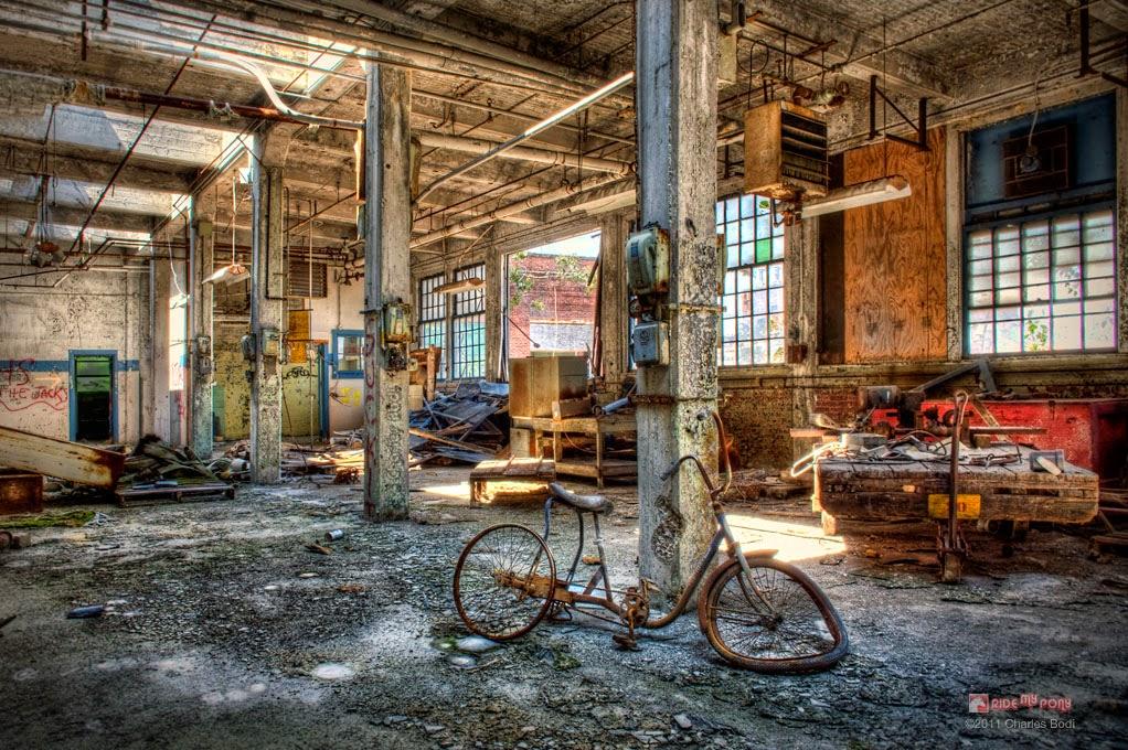 photo de charles bodi representant un vieux velo dans une usine abandonnée