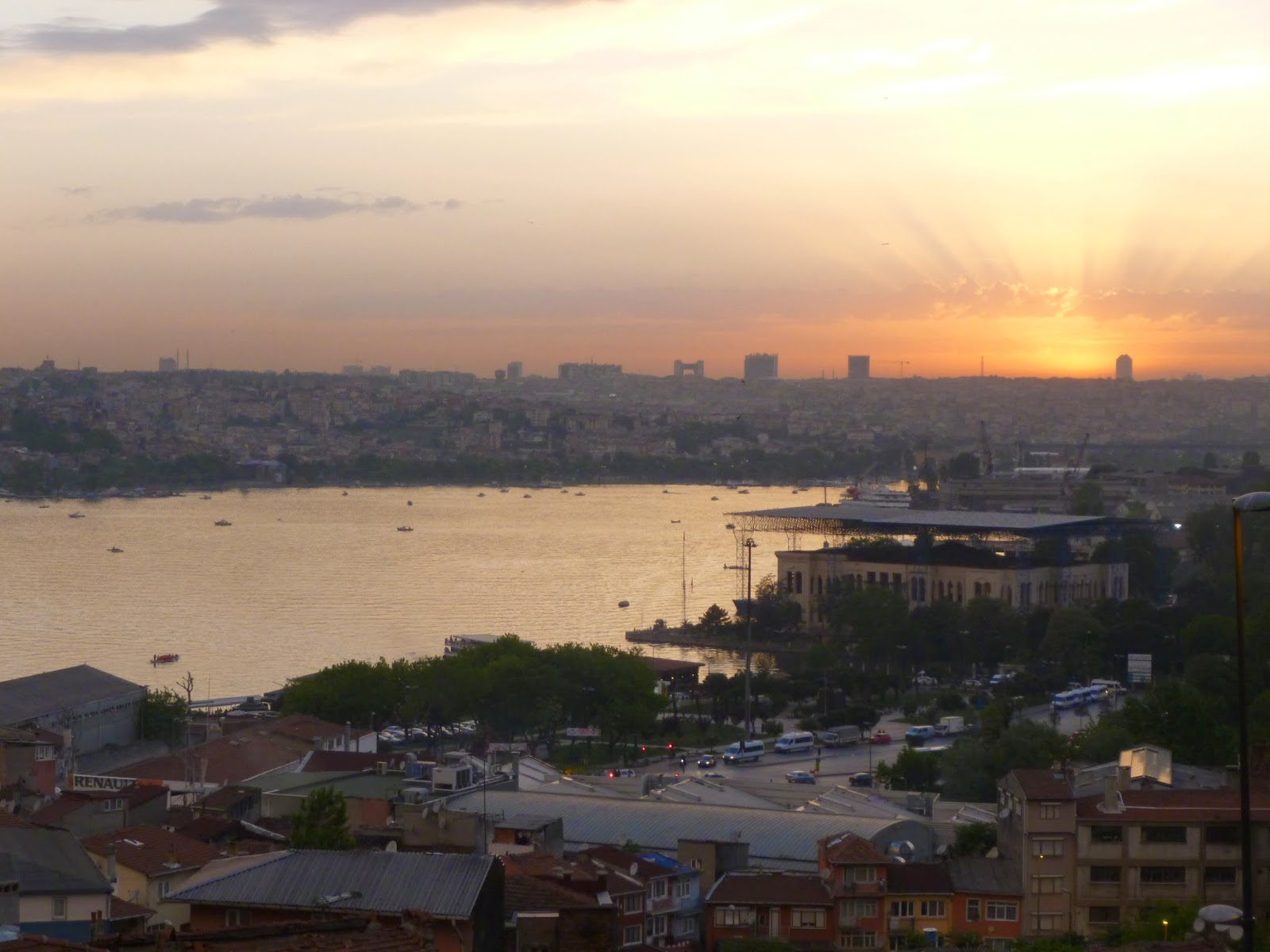 Picture of the Golden Horn, a bay in Istanbul, from a hill above, surrounded by the city and lit red and orange by the sunset.