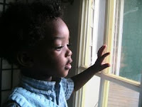 Black baby looking out window. Stock Photo credit: Springj