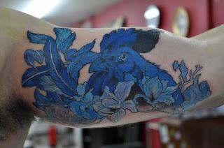 tatuagem de galo azul na parte interna do braço