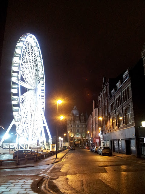 Ferris wheel lighting up a street at night in Leeds