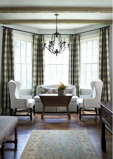 Living room with gingham curtains, white dueling armchairs, a rustic coffee table and chandelier