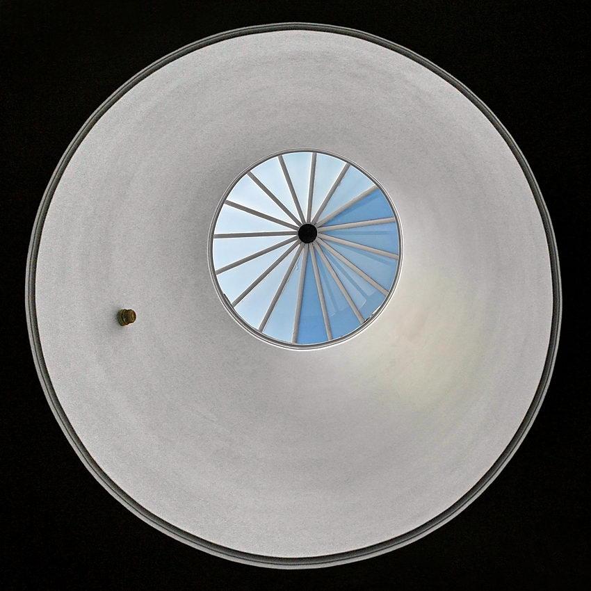 Foto quadrada numa vista de baixo, com a clarabóia circular centrada na imagem