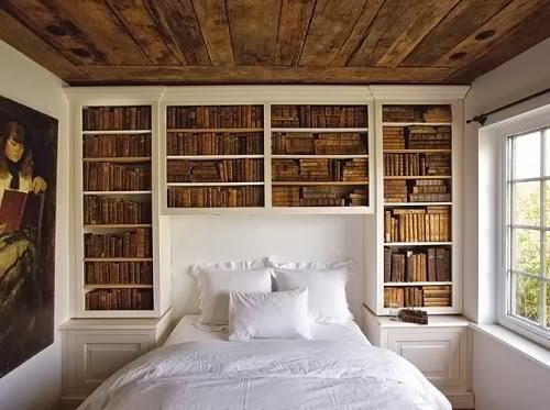 white walls, white bedding, vintage decor, distressed ceiling, vintage books, vintage painting.